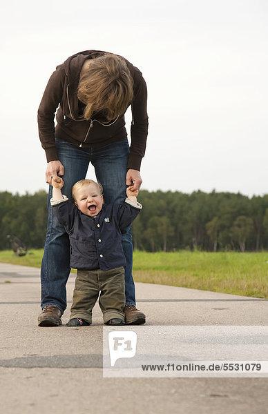 Kleiner Junge  1 Jahr  mit Mutter  lernt das Laufen auf einem Feldweg und jauchzt vor Freude und Zufriedenheit  Deutschland