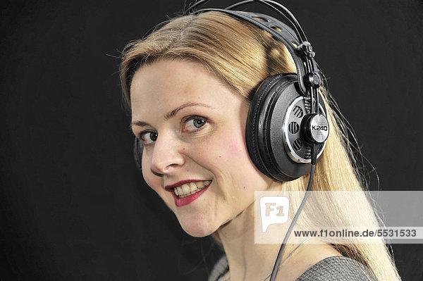 Junge Frau hört mit Kopfhörer Musik