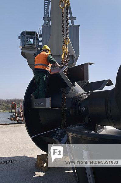 Maschinenteile werden verladen  Arbeiter legt Ketten an und kontrolliert die Befestigung  Hafen Bonn  Nordrhein-Westfalen  Deutschland  Europa