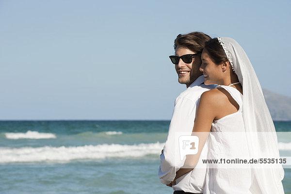Braut und Bräutigam umarmend am Strand