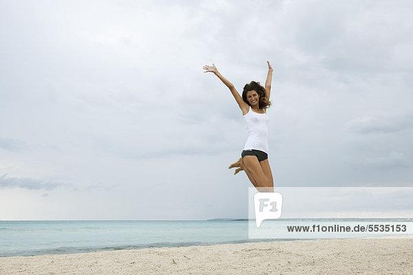 Junge Frau beim Luftspringen am Strand