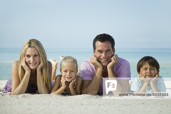 Family lying on sand at the beach  portrait