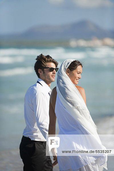 Bride and groom standing on beach  looking at view