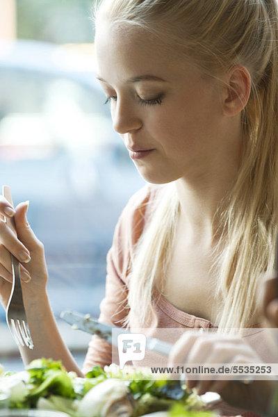 Junge blonde Frau beim Essen mit Gabel und Messer