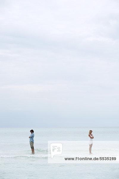 Ein Paar  das im Meer auseinander steht und mit dem Rücken zueinander gedreht ist.