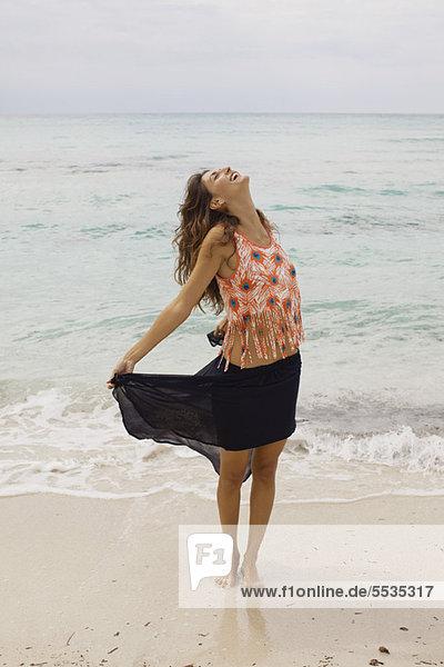 Frau am Strand stehend mit geschlossenem Kopf und geschlossenen Augen