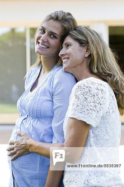 Mutter legt die Hand auf den Bauch der schwangeren Tochter.