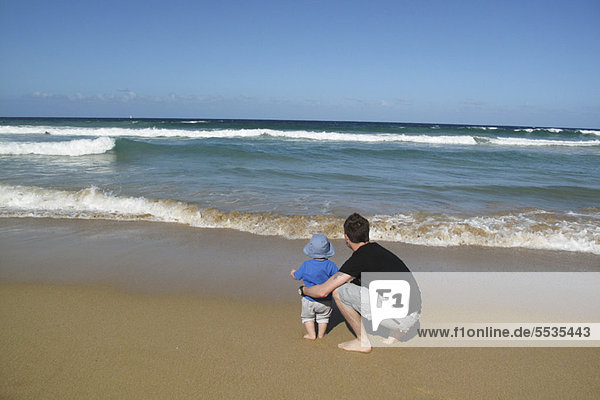 Father and baby at the beach  looking at sea