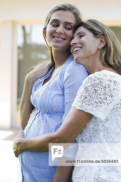 Mutter umarmt schwangere Tochter