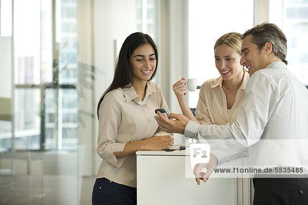 Kollegen schauen in der Kaffeepause gemeinsam aufs Handy
