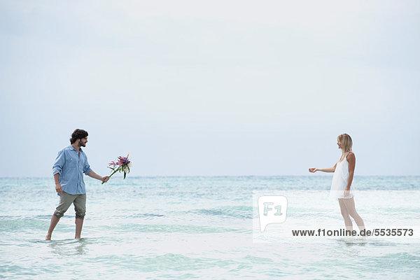 Pärchen  die im Meer aufeinander zugehen  Mann  der einen Strauß aushält