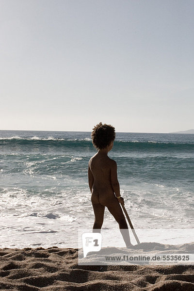 Little girl standing naked at the beach  rear view