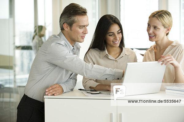 Kollegen  die gemeinsam am Laptop arbeiten