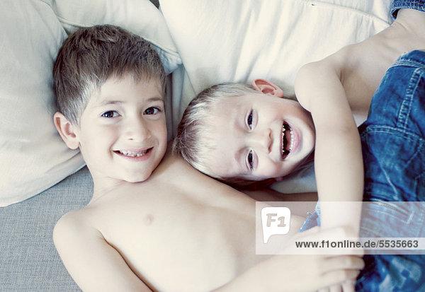Junge Brüder auf dem Bett liegend  Porträt