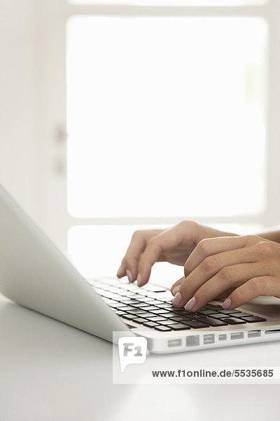 Frauenhände beim Tippen auf dem Laptop