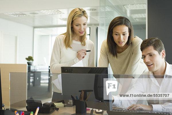 Kollegen  die gemeinsam am Computer arbeiten
