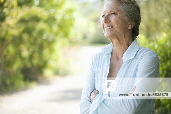 Seniorin lächelnd und in die Ferne blickend