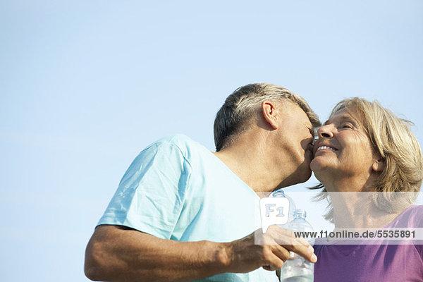 Älterer Mann  der die Wange seiner Frau küsst.