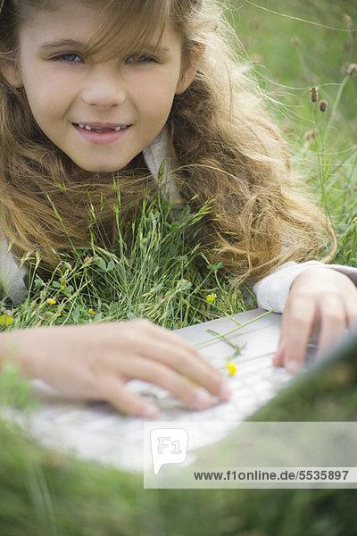 Mädchen im Gras liegend  mit Laptop-Computer  Portrait