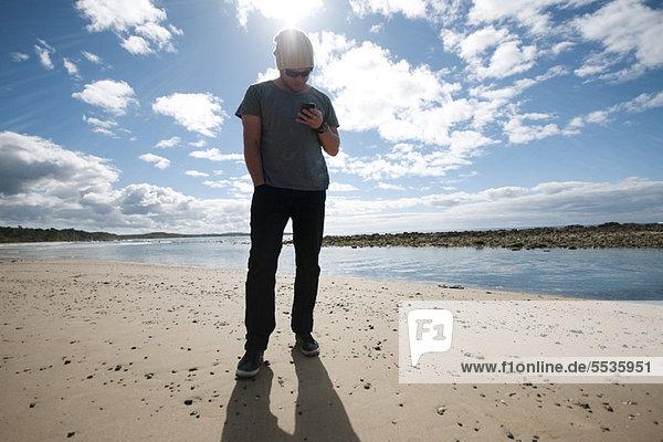 Mann steht am Strand und schaut auf sein Handy.