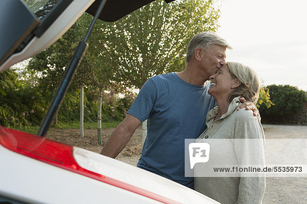 Senior couple standing beside car  man kissing woman's forehead