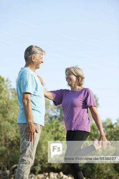 Seniorenpaar im Freien  Frau hält sich an Mann zur Unterstützung beim Dehnen fest