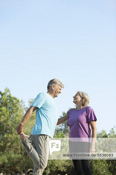 Seniorenpaar beim gemeinsamen Stretching im Freien