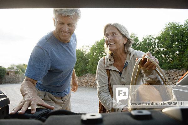Seniorenpaar beim Verladen von Säcken ins Auto