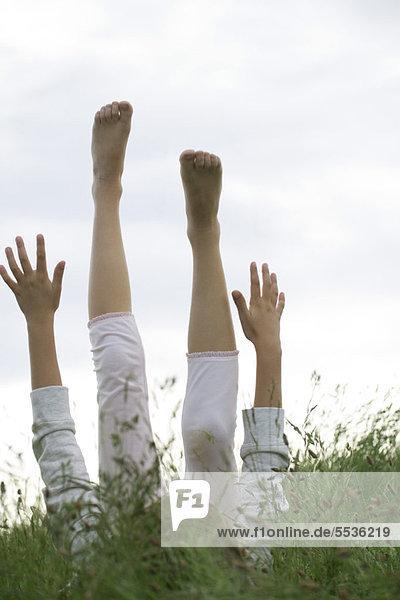 Mädchen auf dem Rücken liegend im hohen Gras mit erhobenen Armen und Beinen