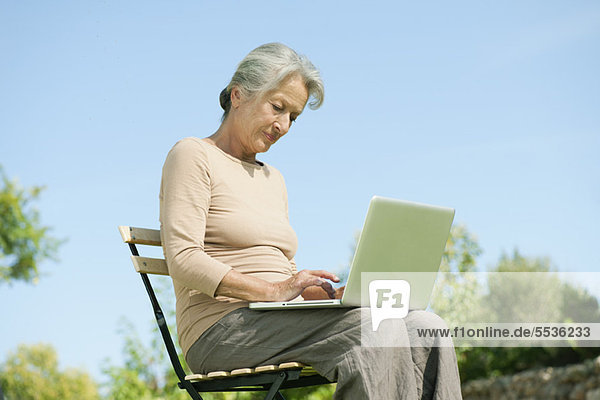 Senior Frau mit Laptop im Freien