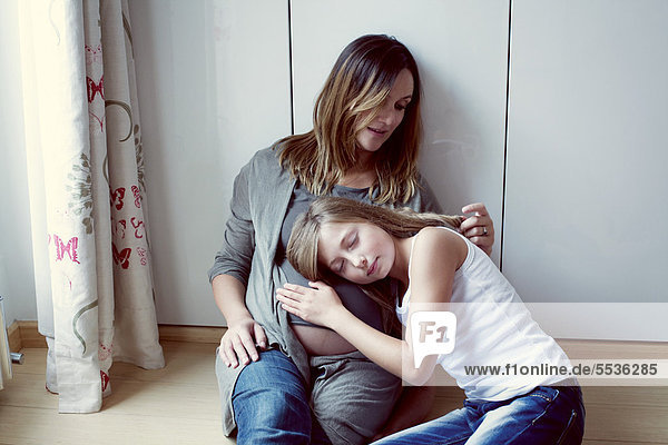 Daughter listening to pregnant mother's abdomen  mother caressing daughter's hair  portrait