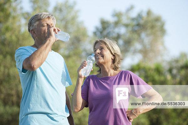 Seniorenpaar trinkt Flaschenwasser im Freien