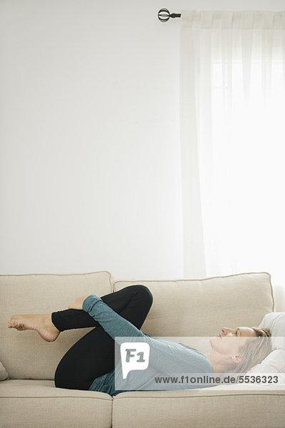 Reife Frau  die auf der Couch liegt und die Knie umarmt.