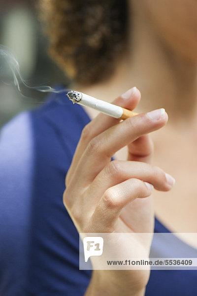 Frauenhand mit angezündeter Zigarette