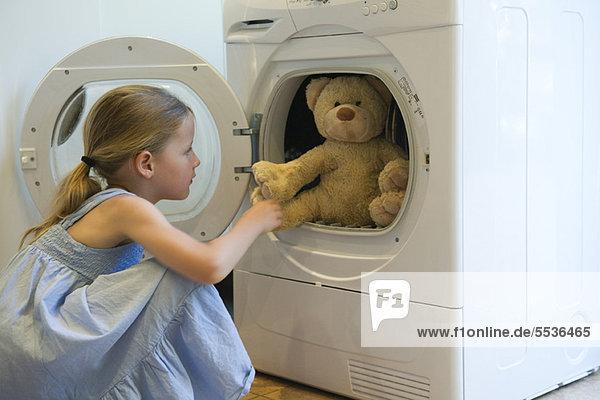 Kleines Mädchen nimmt Teddybär aus dem Trockner