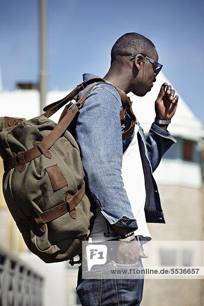 Seitenansicht des jungen Mannes mit Rucksack