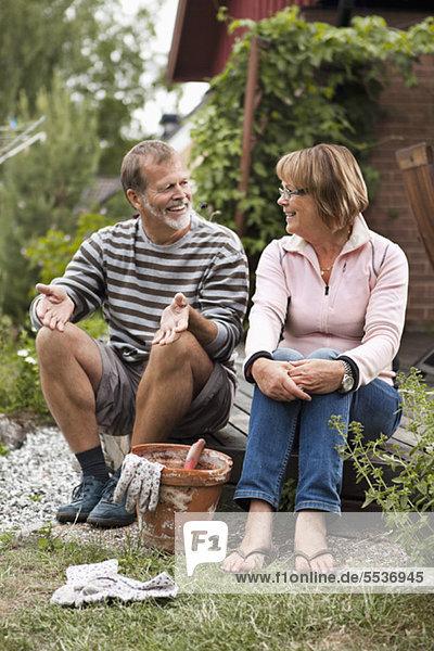Aktives Seniorenpaar spricht im Garten über Gartenarbeit
