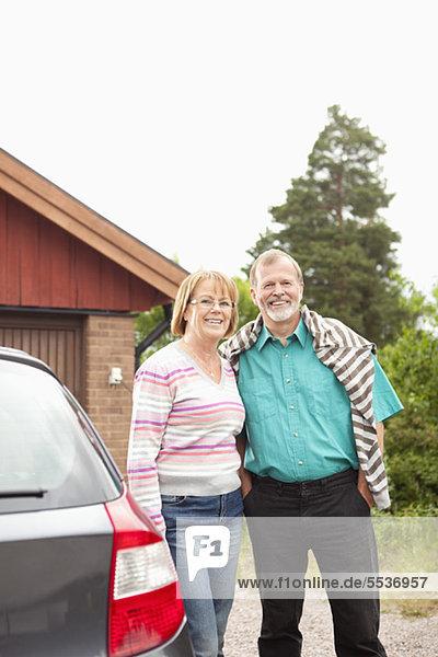 Vorderansicht des lächelnden älteren Paares in der Nähe des Autos