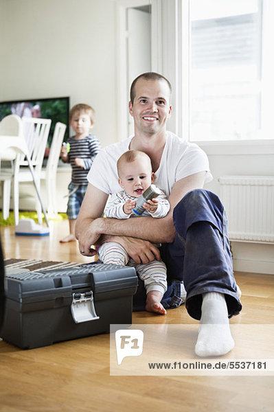 Vater und Sohn sitzend am Werkzeugkasten mit Junge im Hintergrund
