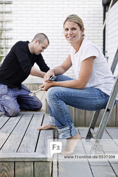 Glückliche Frau mit Mann im Hintergrund