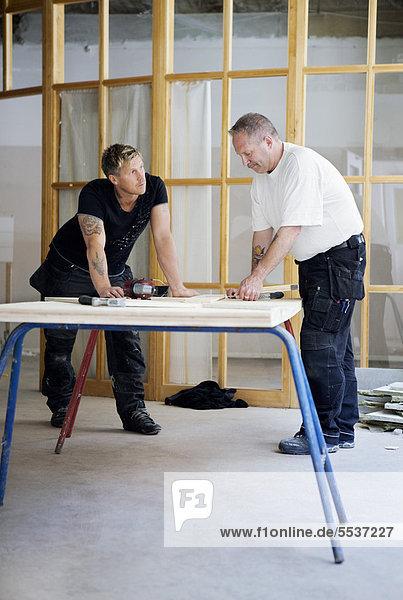 Schreiner arbeiten in der Werkstatt zusammen