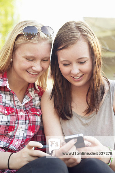 Two girls using cell phones