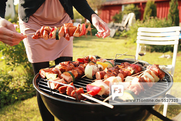 Midsection of holding skewer with barbecue grill