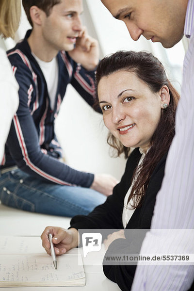 Porträt einer Geschäftsfrau lächelnd mit Kollegen im Hintergrund