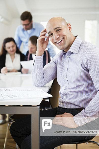 Porträt eines mittelgroßen Mannes  der lächelt  mit einem Geschäftstreffen im Hintergrund