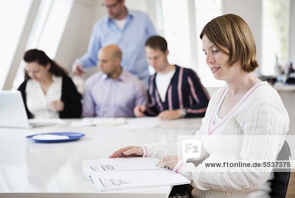 Mittlere erwachsene Frau beim Lesen mit Geschäftskollegen am Konferenztisch