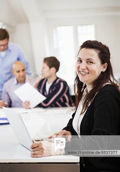 Lächelnde Geschäftsfrau mit Laptop und Kollegen am Konferenztisch im Hintergrund
