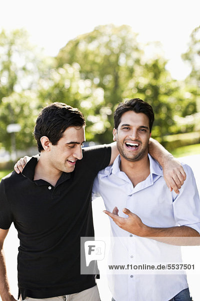 Front view of cheerful male friends with arm around
