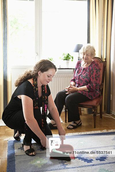 Großmutter schaut  während Enkelkind Teppichreinigung