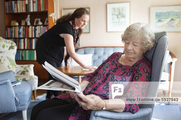 Seniorin beim Zeitungslesen und Enkelin beim Putzen im Hintergrund